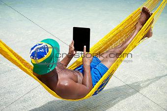 Brazilian Man Relaxes Using Tablet in Hammock on Beach