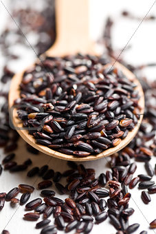 black rice on wooden spoon