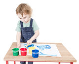 child making painting on small desk