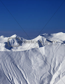 Off-piste slope with traces of skis and snowboards in sun day
