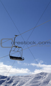 Chair lift and snowy mountains at nice day