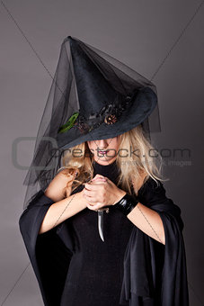 glamorous girl in black shiny dress with a dagger in his hand