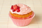 cupcake with whipped cream and redcurrant
