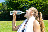 Athletic woman drinking water after a workout
