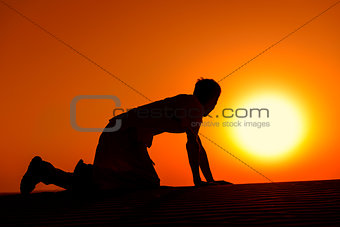 Tired and weaken man on all fours on sunset