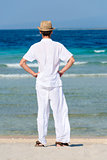 Man in white suit on a tropical beach, back view