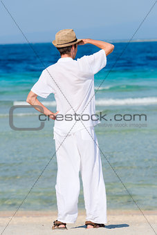 Man in a white suit against the sea
