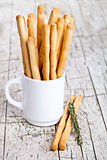 cup with bread sticks grissini and rosemary