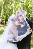 a happy newly-married couple under the veil