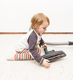 young child cleaning vacuum cleaner