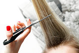 woman cutting long hair with scissors