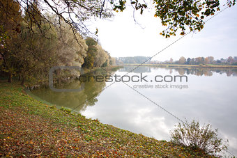Autumn landscape with water and reflection of clouds