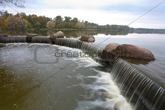 Waterfall against overcast sky in autumn