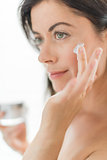 attractive woman in her forties applying  face cream