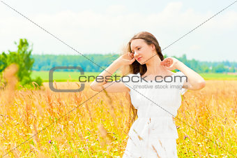 beautiful young Russian girl in a field with gold ears of wheat