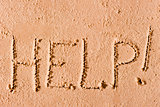 "on the wet sand written the word ""Help!"" by the sea"