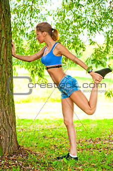 beautiful girl doing warm-up at the tree park in sportswear