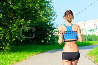 athletic girl in a top and shorts running on the road in the park, not far from the city