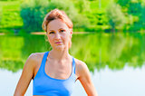 portrait of a beautiful girl on the nature of sports on the lake background