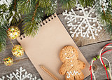 Christmas fir tree, decor and blank notepad on wooden board back