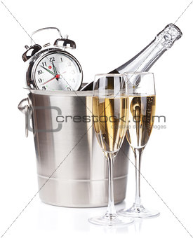 Champagne bottle in bucket, two glasses and alarm clock