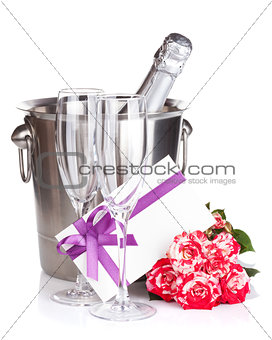 Champagne bottle, two glasses, letter and red rose flowers