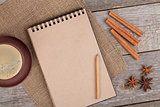 Blank notepad with coffee cup and spices on wooden table