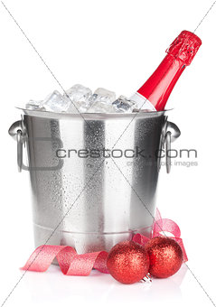 Champagne bottle in ice bucket and christmas decor