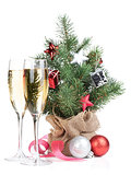 Small christmas tree with decor and two champagne glasses