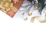 Gift box and christmas decor under snowy fir tree