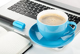 Blue coffee cup, laptop and office supplies