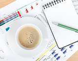 Coffee cup and notepad over papers with numbers and charts