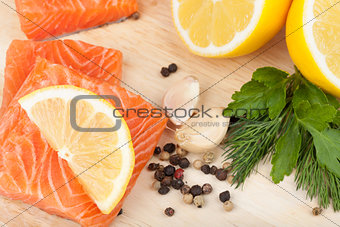 Salmon on cutting board with lemons and herbs