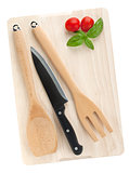 Cooking utensils and tomato with basil over cutting board