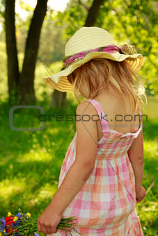beautiful little girl on nature with a bouquet of flowers