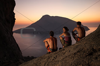 Three rock climbers wearing safety harness having rest at sunset. With picturesque view of Telendos Island in front. Kalymnos Island, Greece.