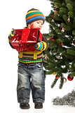 Cute little boy with gift near Christmas tree