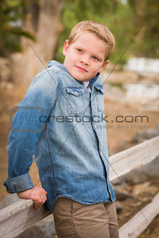 Handsome Young Boy Against Fence in Park