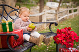 Young Toddler Child Sitting on Bench with Christmas Gifts Outsid