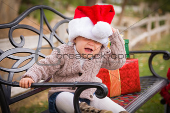 Young Child Wearing Santa Hat Sitting with Christmas Gifts Outsi