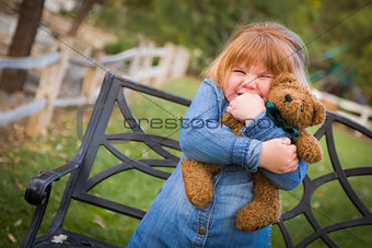 Cute Smiling Young Girl Hugging Her Teddy Bear Outside