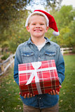 Young Boy Wearing Holiday Clothing Holding Christmas Gift Outsid