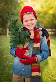 Young Boy Wearing Holiday Clothing Holding Small Christmas Tree
