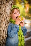 Young Girl Wearing Green Scarf and Hat Eating Apple Outside