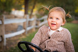 Young Toddler Laughing and Playing on Toy Tractor Outside