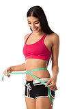 Beautiful young girl checking her waistline with measuring tape