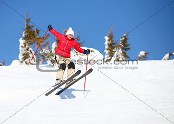 Young female skier jumping on snowy slope