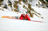 Cute young female skier looking at the camera after falling down on mountain slope