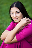 Portrait of beautiful young woman sitting on grass in park