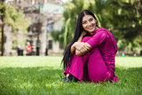 Happy young girl sitting on grass in park